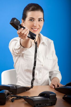 Businesswoman in office answering a call - Focus is on the phone Stock Photo - 4980295