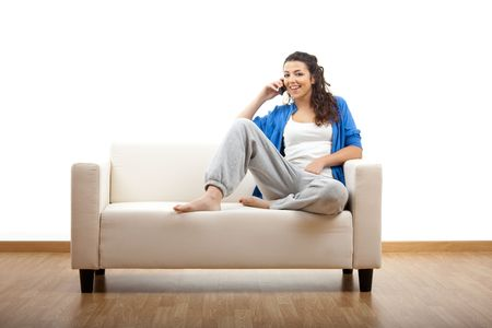 Portrait of a girl seated on the couch and making a phone call photo