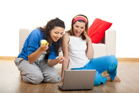 Two beautiful young women sitting on floor working with a laptop Stock Photo - 5067496