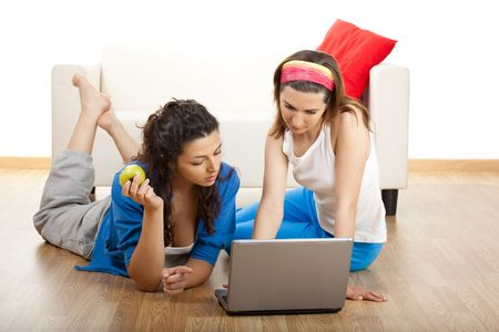 Two beautiful young women sitting on floor working with a laptop photo