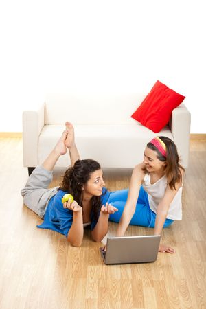 Two beautiful young women sitting on floor working with a laptop Stock Photo - 5067521