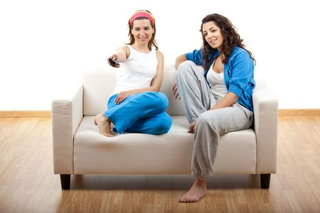 Two beautiful young women relaxing on the couch holding a remote control - isolated on white photo