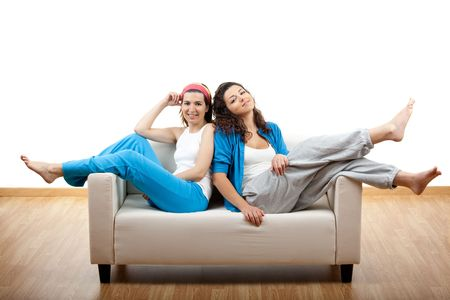 Two beautiful young womens sitting on a sofa photo