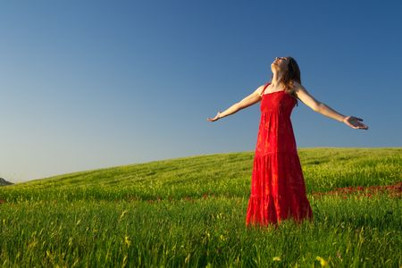 Beautiful young woman relaxing on the field with both arms open Stock Photo - 5067487