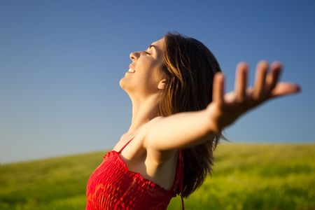 Portrait of beautiful young woman relaxing on the field with both arms open photo