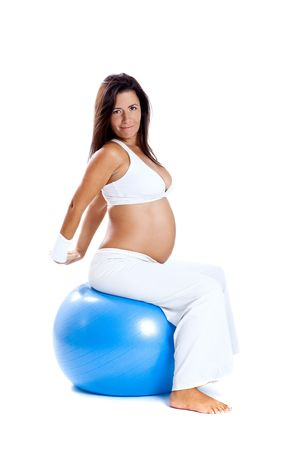 Beautiful pregnant woman making exercises on a fitness ball photo