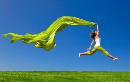 Schöne junge Frau, die auf einer grünen Wiese mit einem farbigen Gewebe springen