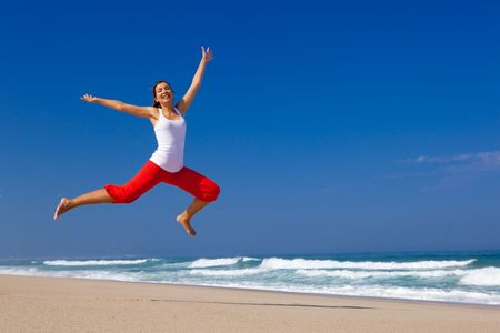 Beautiful young woman jumping on  the beach Stock Photo - 6631684