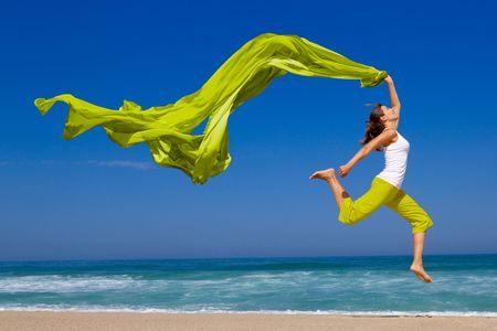 Schöne junge Frau, die am Strand mit einem farbigen Gewebe springen