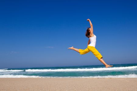 Beautiful young woman jumping on  the beach Stock Photo - 6631362
