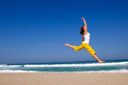 Hermosa mujer joven saltando en la playa Foto de archivo