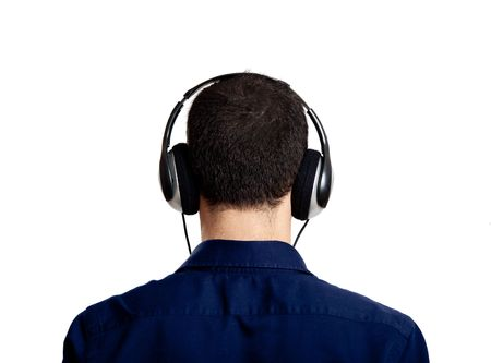 Back view of a young man listening music with headphones, isolated on white photo