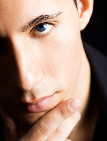 Fashion portrait of a young man with blue eyes isolated on black background photo