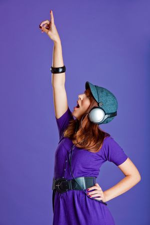Beautiful and happy young woman listen music with headphones, over a violet background photo