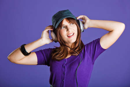Beautiful and happy young woman listen music with headphones, over a violet background Stock Photo - 6809232