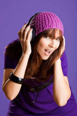 Beautiful and happy young woman listen music with headphones, over a violet background Stock Photo - 6809278