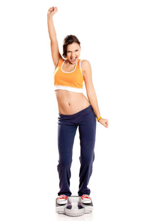 Portrait of a beautiful athletic girl checking her weight, isolated on white Stock Photo - 6809156