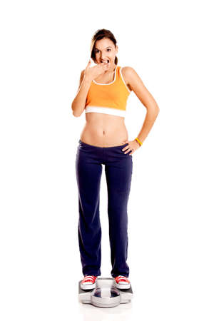 Portrait of a beautiful athletic girl checking her weight, isolated on white Stock Photo - 6809081