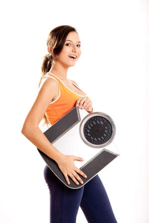 Portrait of a beautiful athletic girl holding a scale, isolated on white Stock Photo - 6809086