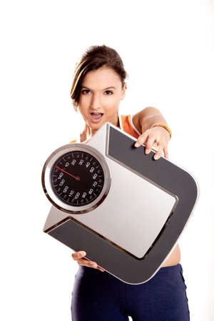 Portrait of a beautiful athletic girl holding a scale, isolated on white Stock Photo - 6809157
