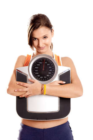 Portrait of a beautiful athletic girl holding a scale, isolated on white Stock Photo - 6809150