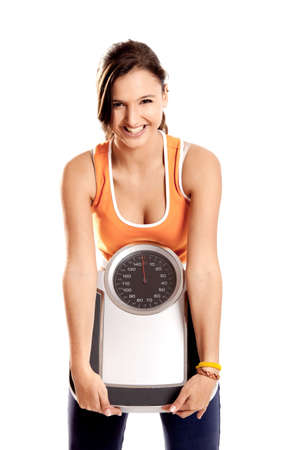 Portrait of a beautiful athletic girl holding a scale, isolated on white Stock Photo - 6809183