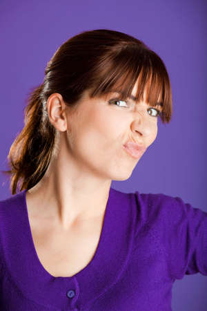 Portrait of a beautiful woman with a funny face, over a violet background Stock Photo - 6809385