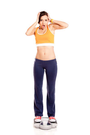 Portrait of a beautiful athletic girl checking her weight, isolated on white Stock Photo - 6809490