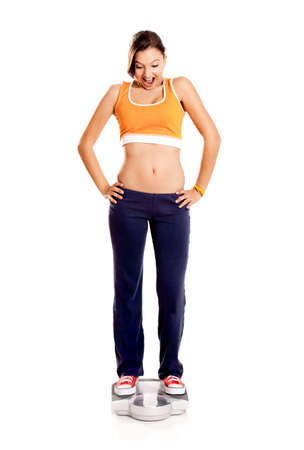 Portrait of a beautiful athletic girl checking her weight, isolated on white Stock Photo - 6809339