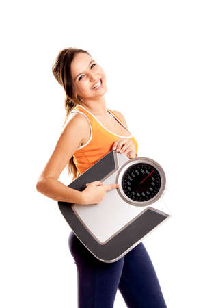 Portrait of a beautiful athletic girl holding a scale, isolated on white photo