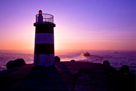 Beautiful landscape picture of a lighthouse at sunset photo