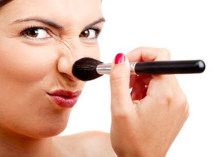 Portrait of a beautiful woman applying make-up with a brush and making a funny face photo