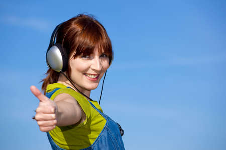 Portrait of a happy woman listen music over a beautiful blue sky with thumbs up photo