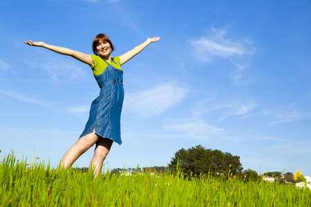 Beautiful happy woman on a green meadow with arms open Stock Photo - 6882472