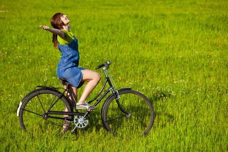 Young woman with a vintage bicycle relaxing on a green meadow photo