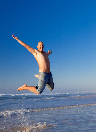 Young man jumping on the beach Stock Photo - 7064361