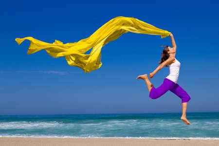 scarf beach: Hermosa mujer joven saltando sobre la playa con un tejido color Foto de archivo