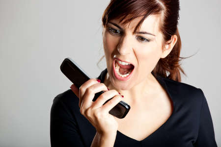 mad girl: Portrait of a mad woman shouting to the cellphone Stock Photo