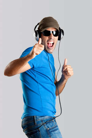 Happy young man with thumb up and listening music photo