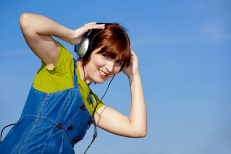 Portrait of a happy woman listen music over a beautiful blue sky photo