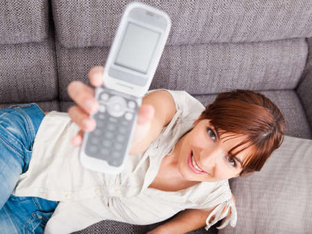 Top view of a beautiful woman lying on sofa and showing a cellphone photo
