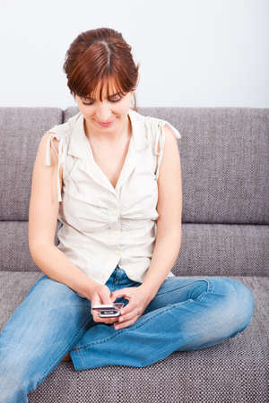 Portrait of a happy woman sitting on sofa and holding a cellphone photo