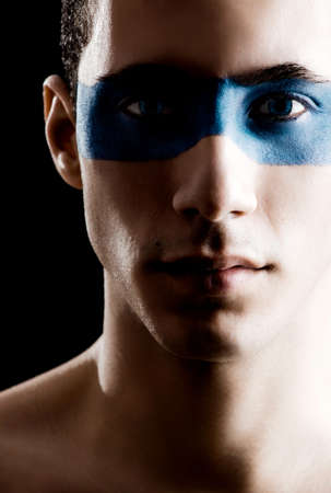 Fashion portrait of a young man with a blue make-up photo