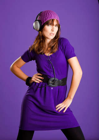 Beautiful fashion young woman listen music with headphones, over a violet background photo