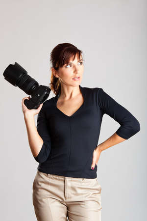 Portrait of a beautiful and attractive young woman holding a camera photo