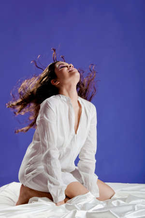 Beautiful and happy young on a bed, moving her hair photo