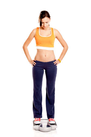 Portrait of a beautiful athletic girl checking her weight, isolated on white Stock Photo - 7150254