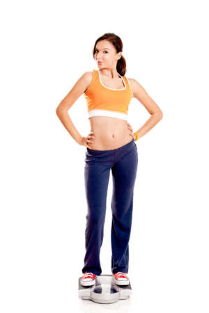 Portrait of a beautiful athletic girl checking her weight, isolated on white Stock Photo - 7150251