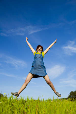 Happy young woman jumping and enjoying the spring on a beautiful day photo