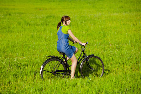 Happy young woman on a green meadow riding a bicycle Stock Photo - 7150331